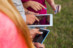 Three friends with electronic gadget in park. Close up. Royalty Free Stock Photo