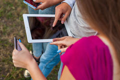 Three friends with electronic gadget in park. Close up. Stock Photography
