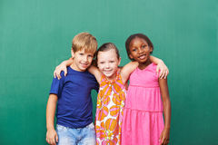 Three friends embracing in kindergarten. Three happy friends embracing in kindergarten in front of a green wall Stock Photos