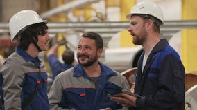 Three friends engineers in heavy industry factory, smile and discuss plans