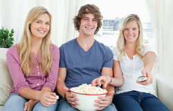 Three friends enjoying popcorn together Stock Photo