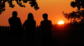 Three friends enjoying the sunset. Silhouettes of a man and two women watching the sunset stock image