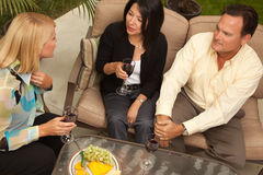 Three Friends Enjoying Wine on the Patio Stock Image