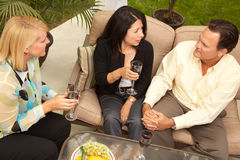 Three Friends Enjoying Wine on the Patio Stock Images