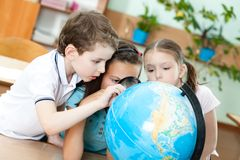 Three friends examine a school globe. Three friends examine a school terrestrial globe Stock Photos