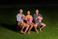 Three friends in exterior cinema Stock Image