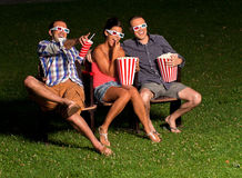 Three friends in exterior cinema Royalty Free Stock Photography