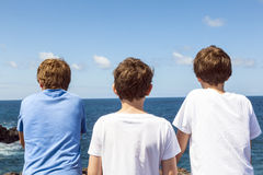 Three friends in front of the ocean in Lanzarote Royalty Free Stock Photo