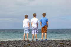 Three friends in front of the ocean in Lanzarote Stock Image