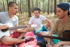Three friends with guitar sitting on blanket in forest Stock Images