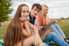 Three friends with guitar sitting on blanket in the park. Royalty Free Stock Photo