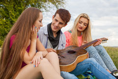 Three friends with guitar sitting on blanket in the park. Stock Image