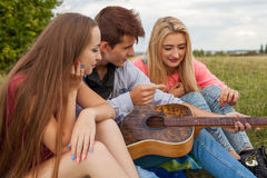 Three friends with guitar sitting on blanket in the park. Royalty Free Stock Photos