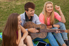 Three friends with guitar sitting on blanket in the park. Royalty Free Stock Photography