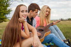 Three friends with guitar sitting on blanket in the park. Royalty Free Stock Image