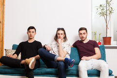Three friends hanging out together in nice confortable room Royalty Free Stock Photo