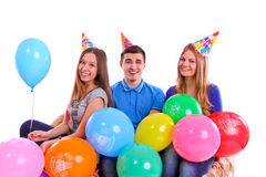Three friends in hats with balloons sitting on the couch Stock Image