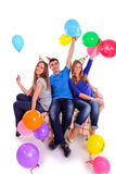 Three friends in hats with balloons sitting on the couch Stock Photo