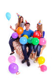 Three friends with hats and balloons sitting on th Royalty Free Stock Photo