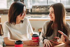 Friends enjoying coffee and friendly talk at cafe. Three friends have good time together sitting at cafe enjoying coffee and friendly talk. People, friendship Stock Photo