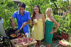 Three friends having a barbecue lunch Stock Photo