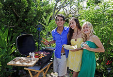 Three friends having a barbecue lunch Stock Images