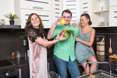 Three friends having fun in the kitchen Stock Image