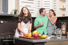 Three friends having fun in the kitchen Stock Photos