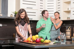 Three friends having fun in the kitchen Royalty Free Stock Photos