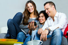 Three friends having fun with a mobile phone stock photos