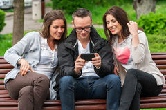 Three friends having a laugh while looking on the smartphone Stock Photo