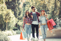 Three friends holding colored bags in hand Royalty Free Stock Image