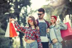 Three friends holding colored bags in hand Royalty Free Stock Photo