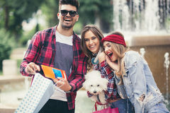 Three friends holding colored shopping bags in hand Stock Image