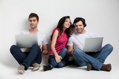 Three friends holding laptops expressions Royalty Free Stock Images