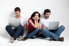 Three friends holding laptops expressions Stock Photos