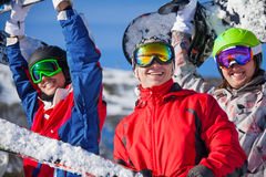 Three friends holding snowboards and skies Royalty Free Stock Photography