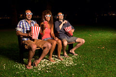 Three Friends In Exterior Cinema Stock Images