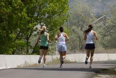 Three friends jogging. Three women running on a jogging path Stock Photos
