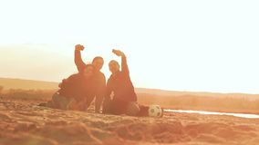 Three friends laugh make selfie phone slow motion video. Three friends, two guys and a girl laugh make selfie on phone sitting on the sand at sunset slow motion stock video footage