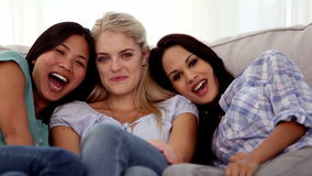 Three friends laughing together while watching television stock video