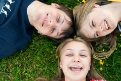 Three friends lay on a grass Stock Images