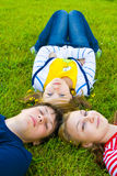 Three friends lay on a grass Stock Photos