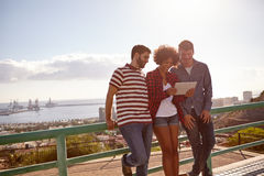 Three friends leaning against a railing Royalty Free Stock Photography