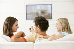 Three friends in living room watching television Stock Image