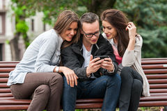 Three friends looking at an image on a smartphone while sitting on a park bench Stock Photo