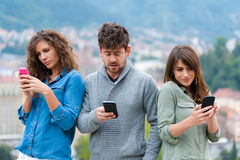 Three Friends looking at smartphone Stock Image