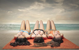 Three friends lying at the beach Royalty Free Stock Image