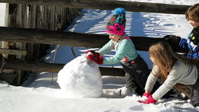 Three Friends are Making a Huge Snowball Together. Closeup Portrait of Two Girls and One Boy Playing Ourdoors in the. Winter Time, HD stock video footage