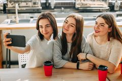 Three friends making selfie drink coffee at cafe stock photo